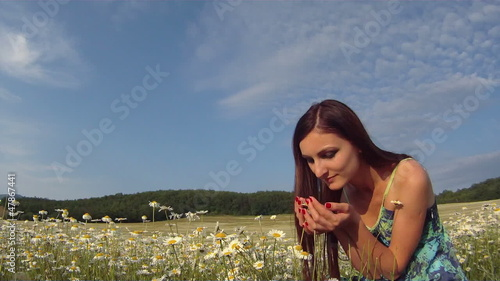 Woman smelling daisies in a field