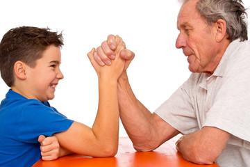 Generationenkonflikt - Großvater und Enkel beim Armdrücken