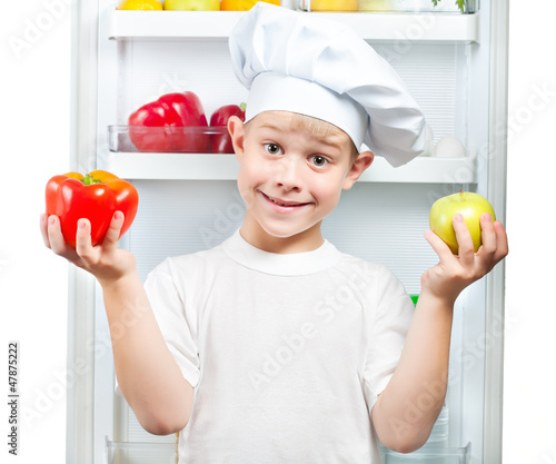 cute smaster chef is choosing food near the open refrigerator