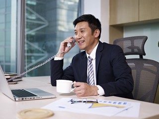 asian businessman talking on phone in office
