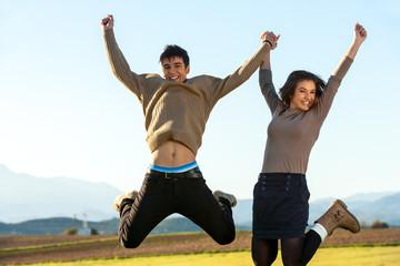Young couple hanving fun jumping.