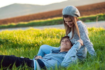 Young couple relaxing in green grass field.
