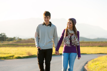 Young couple wandering in sunny countryside.