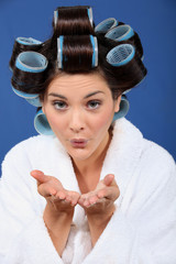 Woman with her hair in rollers blowing a kiss