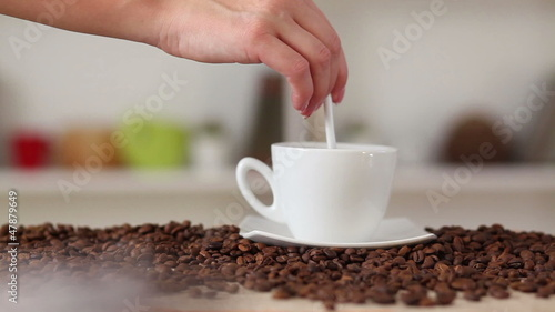 Woman hand mixing coffee with spoon