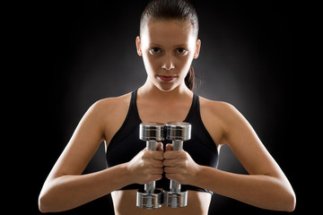 Young woman exercise weights black background