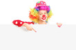 Female clown pointing with finger on a panel