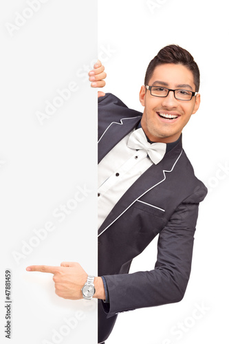 Stylish handsome guy pointing with finger on a panel