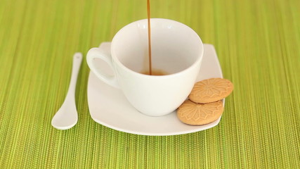 Pouring a cup of fresh hot coffee into cup with cookies
