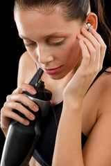 Active woman portrait with water bottle headphones