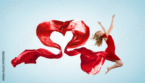 Dancing young woman with flying fabric