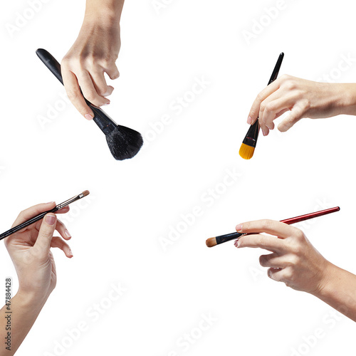 isolated female hands with a brushes for makeup
