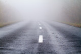 Asphalt road in an autumn fog poster