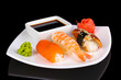 delicious sushi served on plate isolated on black