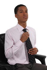 Young businessman straightening tie