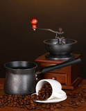 Coffee maker with coffee mill and white cup on wooden table