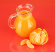 Full jug of tangerine juice, on color background