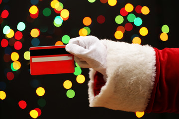 Santa Claus hand holding credit card, on garland background.