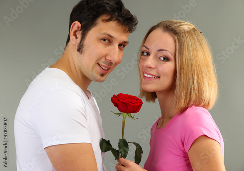 Loving couple with rose on grey background