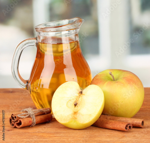 Full jug of apple juice and apple