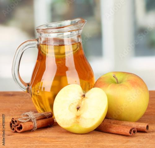Full jug of apple juice and apple