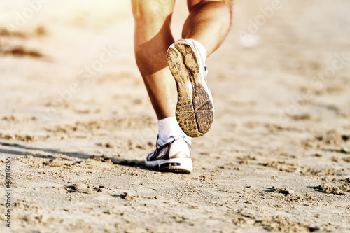 Runner feet running on beach closeup on shoe