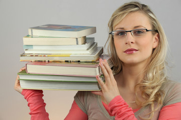 Attractive blond carrying pile of books