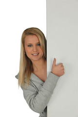 Girl hiding behind panel, studio shot