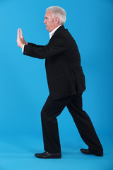 A mature businessman miming.