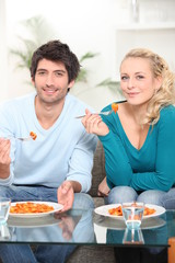 Young couple dining in front of TV