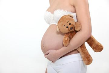 Pregnant woman holding teddy