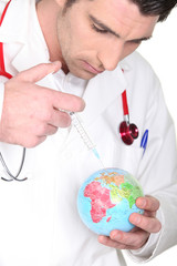 Doctor with syringe and globe