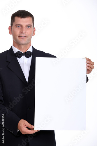 Man wearing bow-tie holding white board