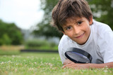 Boy with magnifying glass lying on the grass