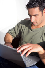 Dark haired man sat with laptop