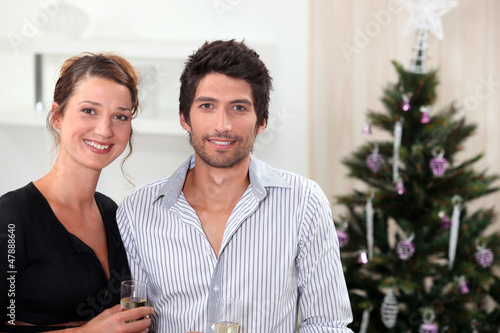 Couple posing in front of their Christmas tree