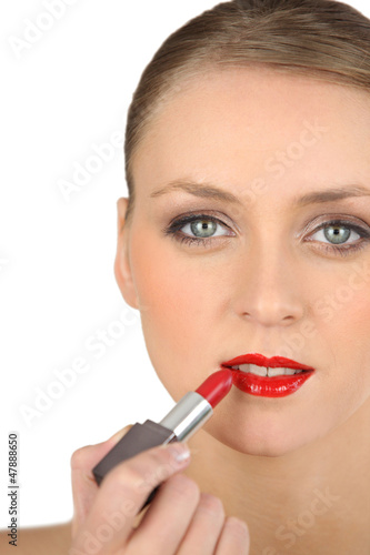 Young woman applying red lipstick