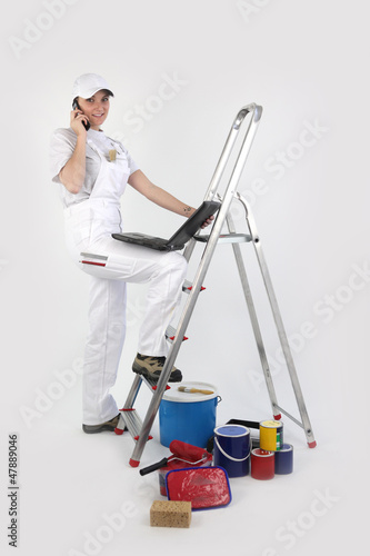 Painter posing by ladder with laptop and mobile