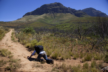 man crawling up mountain