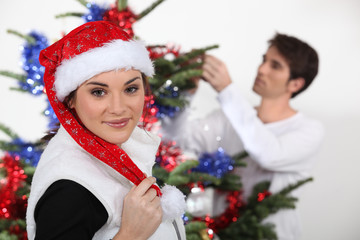 Woman with Christmas cap and man decorating fir