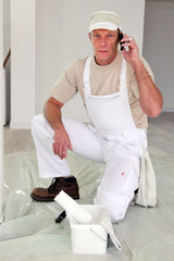 Painter stopping work to make call to supplier
