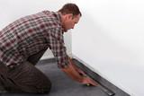 Tradesman laying down linoleum flooring poster