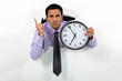 businessman showing clock looks annoyed