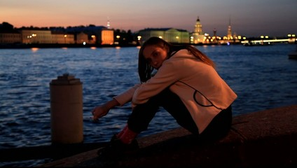 Tired girl sits and smokes on waterfront at night. Rack focus