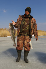 A man with a catch after ice fishing.