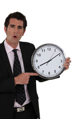 Shocked businessman holding clock