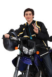Adolescent boy posing with his motorcycle