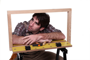 Cabinet maker examining wooden frame