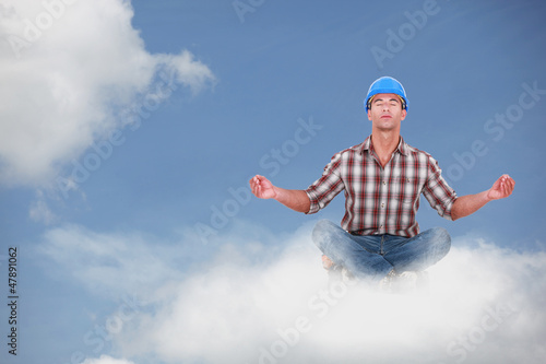 Laborer doing yoga sitting on a cloud