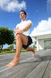 Young man doing stretching exercises by the pool